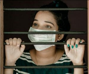 Female behind a gate wearing a face mask during a pandemic